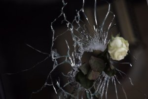 A rose is pictured in a bullet hole in the window of a Japanese restaurant next to the cafe 'La Belle Equipe', Rue de Charonne, on November 15, 2015 in Paris, after a series of gun attacks occurred across the city. French police have identified the first attacker out of the three teams of gunmen who carried out the worst ever attacks ever visited on Paris, which killed 129 people and wounded hundreds more. AFP PHOTO / KENZO TRIBOUILLARD
